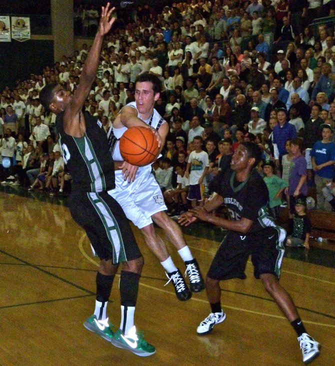 La Costa Canyon guard Jeff Van Dyke throws an acrobatic pass between Inglewood forward Nicholas Smiley (left) and guard Sean Keyes