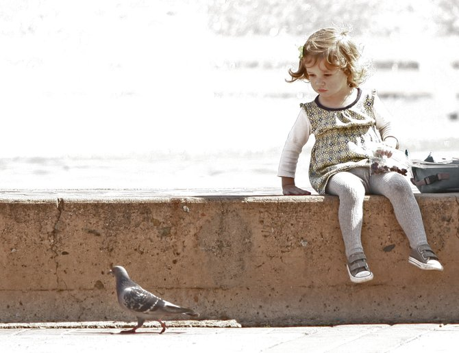 A little girl watches the birds at the fountain in Balboa Park.