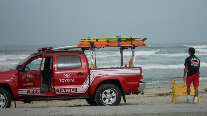 Lifeguard posting Surfing Only sign near Ocean Beach Pier.