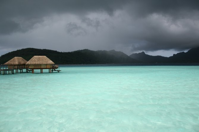 Bora Bora, Tahiti, just before a storm. What you can't see is an opening in the clouds that allowed the sunlight to hit the water and give it its bright turquoise color with the dark clouds above. Photo from 4/15/2011
