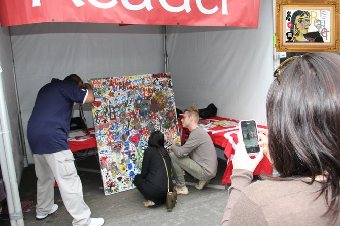Our interactive painting booth was very popular! This is a picture of a girl taking a picture of a guy taking a picture of two people painting on our picture.