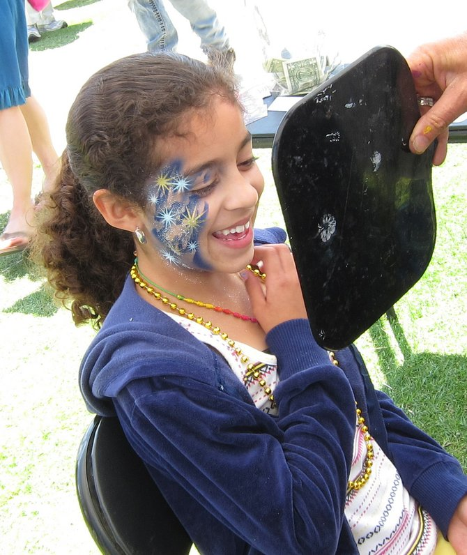 A young customer is delighted with the results of her face painting at Gator By the Bay on Harbor Island.