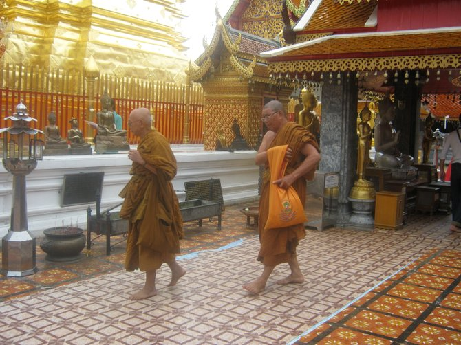 Monks at the Wat Phrathat Doi Suthep in Chiang Mai, Thailand emerge barefoot from the temple.