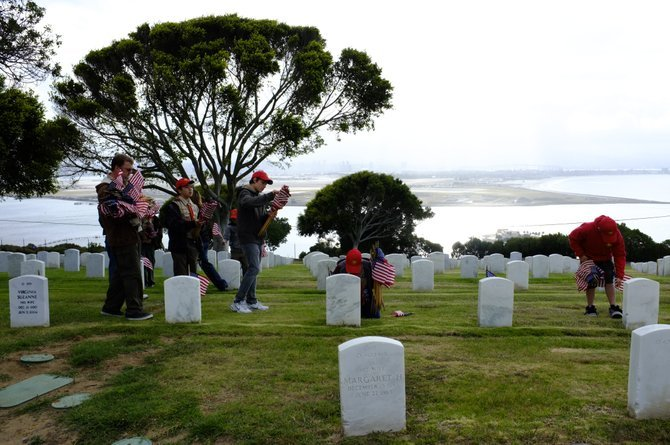 San Diego, CA. Boy Scouts place flags on headstones at Ft. Rosecrans Cemetery in preparation for the Memorial Day holiday.  Boy Scouts, Girl Scouts and volunteers placed flags on more than 67,000 headstones Saturday from 7:45 to 9:30.