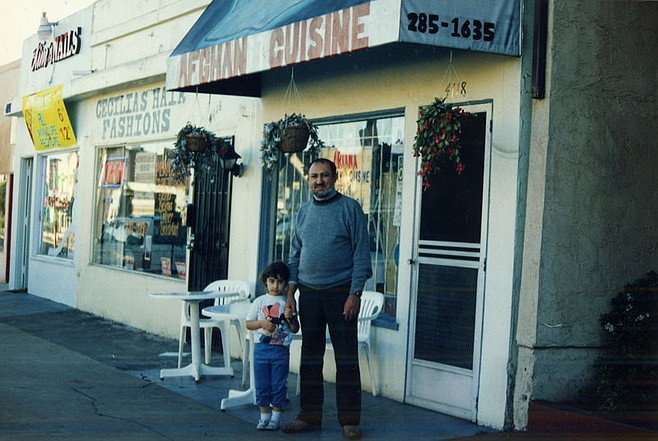 Zia Waleh with his daughter Somiyah outside his café in North Park around 1995. Zia recently returned to his homeland in northern Afghanistan.