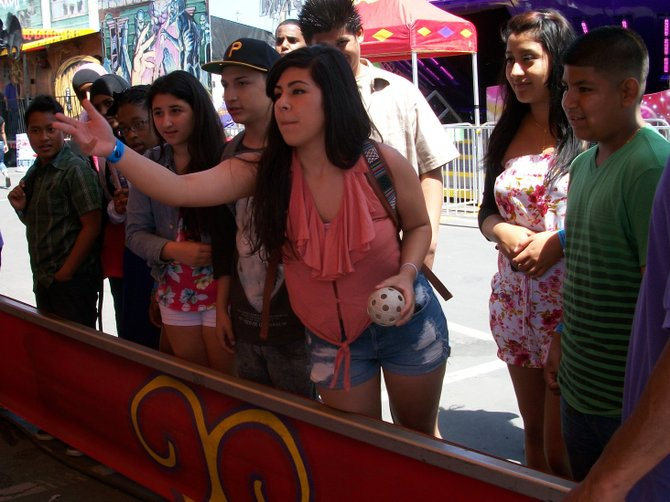 Opening Day of the San DIego County Fair, City Heights teenager Veronica Flores was the first person give up a five dollar bill at the Bank-a-Ball booth. As her 15 friends looked on, her three tossed balls bounced out of the wicker basket, failing to score a large stuffed animal.