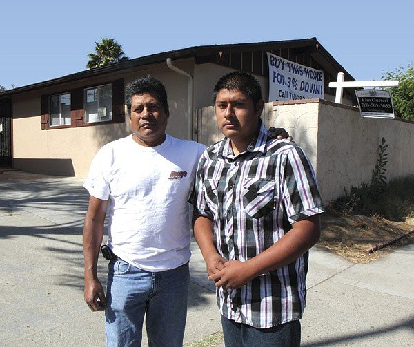 Benito Cristobal and his son Efrem in front of the house they lost to a foreclosure defrauder.