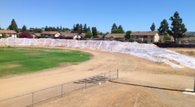 Piled dirt (covered in plastic) sits near the football field, adjacent to a condo complex
