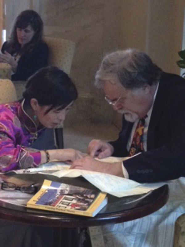 Lhamo Tso consults with Jim Zimmerman, a local specialist with Amnesty International.