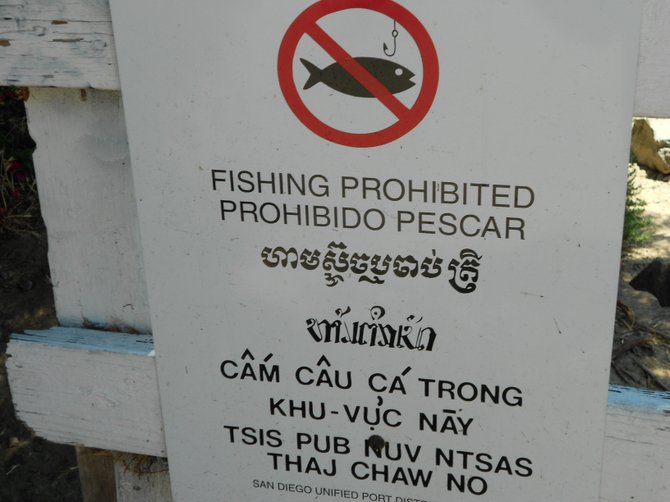 No fishing allowed sign in several languages along Kellogg's Beach in Pt. Loma.