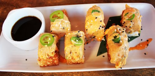 An appetizer of crispy rice with spicy tuna, serrano chili, and ponzu sauce.