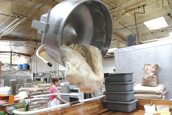 A mixing bowl lift drops 300 lbs. of dough onto a table. It will be cut and placed in plastic bins to be sent to a temperature-controlled proofing room for the dough to rise.