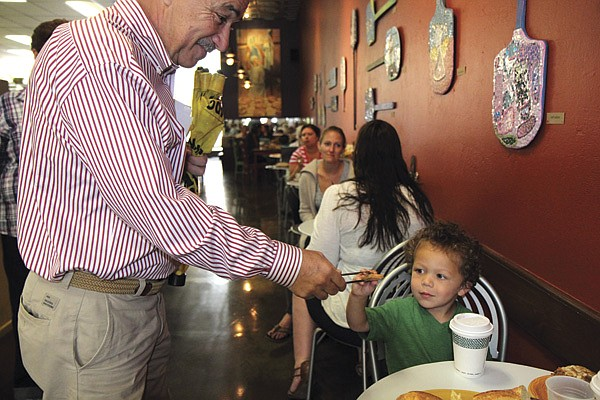 Charles serves a cookie to one of his customers