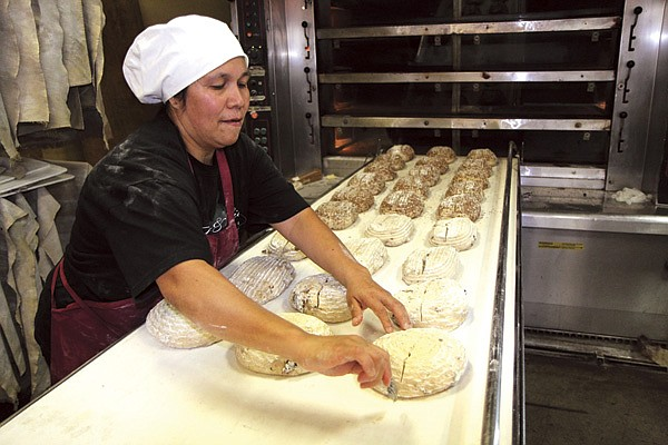 Lorena uses a lame to score the dough before 