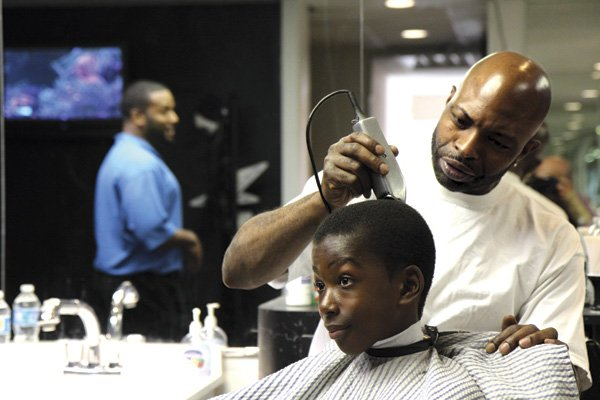 Customers at Milton's barbershop joke, rib each other, 