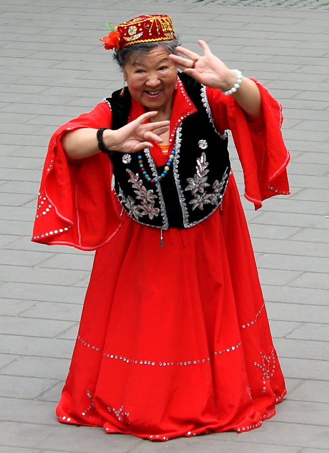 Chinese woman performs for a crowd in a public park outside the Temple of Heaven in Beijing, China.
