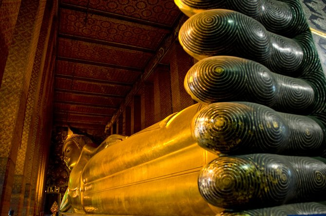 This is the largest indoor representation of Buddha in the world. It is located in Wat Pho, along the Chao Phraya river in Bangkok. It is 160ft long, his feet are 12 feet long.   This picture is the most complete view you can get of the statue, as the whole temple is barely larger than the Buddha it encloses. When you enter, through a small door no larger than a common house's, you are faced directly with the enormity not just of the statue but of the feeling it inspires in Thai people.