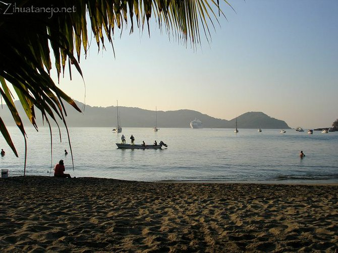 The cruise ship Silver Cloud anchors near the entrance of Zihuatanejo Bay while fishermen cast for bait near Playa Principal.