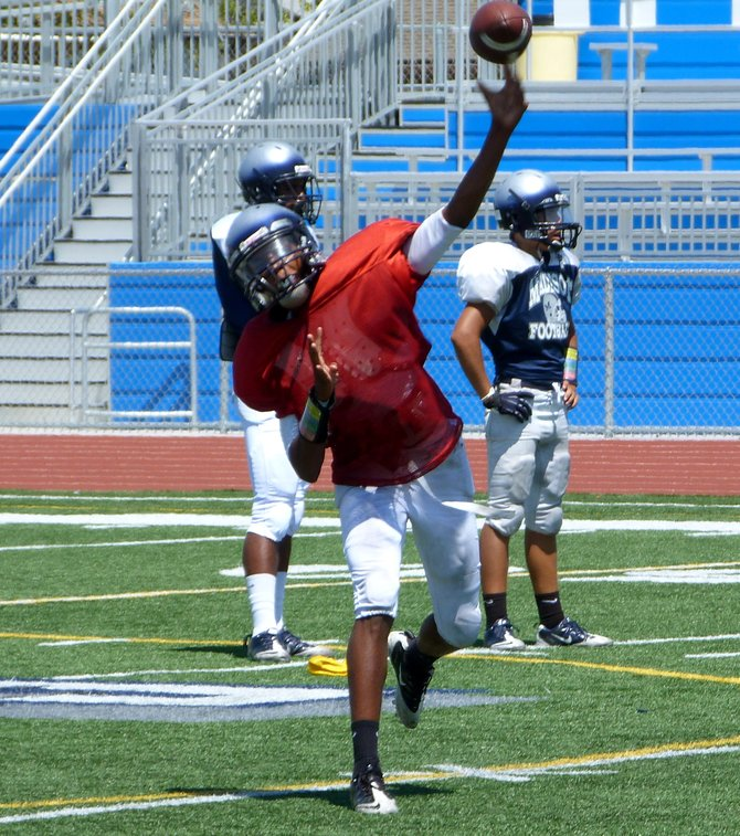 Madison sophomore quarterback Kareem Coles fires a pass during practice