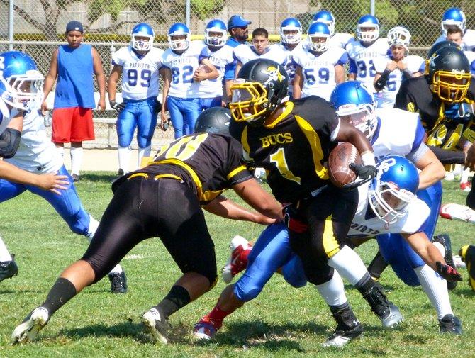 Mission Bay junior running back Devante Kinder breaks through a tackle attempt from an Orange Glen defender