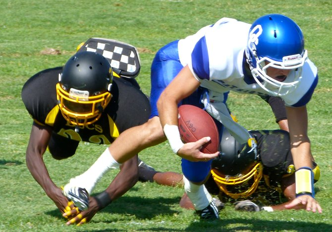Orange Glen senior quarterback Austin Early stumbles forward for extra yards with a pair of Mission Bay defenders in his wake