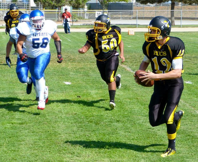 Mission Bay junior quarterback Nick Plum scrambles outside