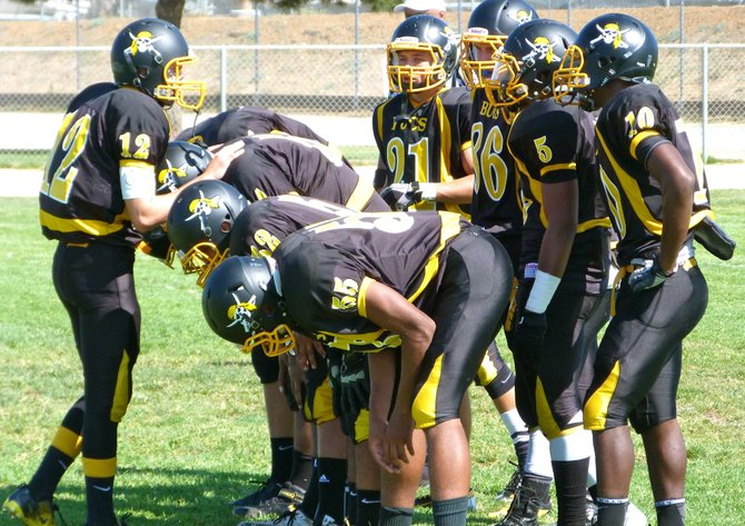 Mission Bay junior quarterback Nick Plum calls out the play in the huddle