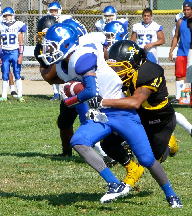 An Orange Glen receiver fights for extra yardage with Mission Bay senior linebacker Jo Jo Griffin latched on to him