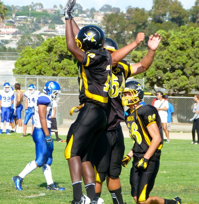 Mission Bay junior receiver Andre Petties-Wilson (10) and senior center Anthony Romero celebrate a Buccaneers touchdown by catching some air