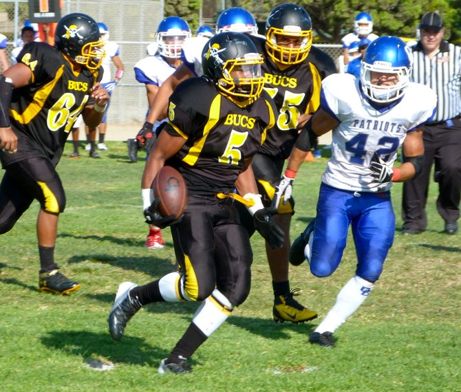 Mission Bay junior running back James Phillips runs the ball outside with Orange Glen senior linebacker Neil Bonahoom giving chase