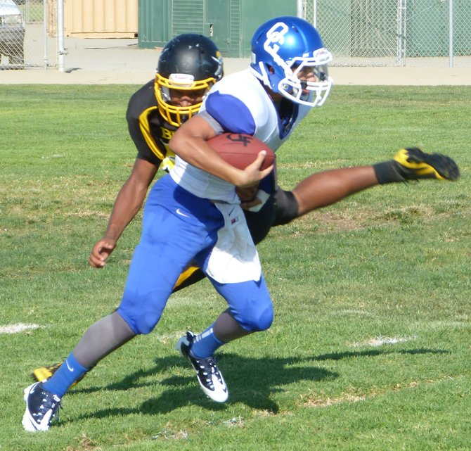 Orange Glen junior quarterback Josh Spina breaks through the tackle of a Mission Bay defender