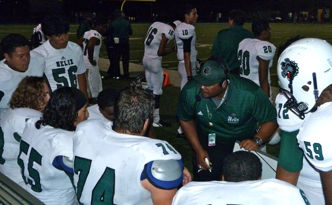 A Helix assistant coach talks things over with the Highlanders offensive line on the bench