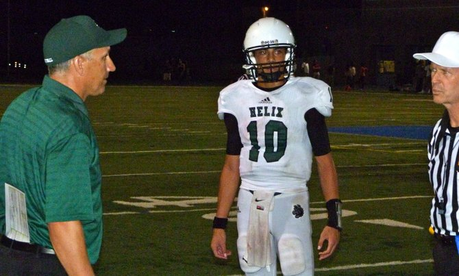 Helix head coach Troy Starr (left) and junior quarterback Josh Harris have a word with the referee along the sidelines