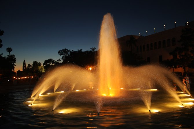 Fountain in Balboa Park, looking west, with the California Bell tower in the background at dusk.