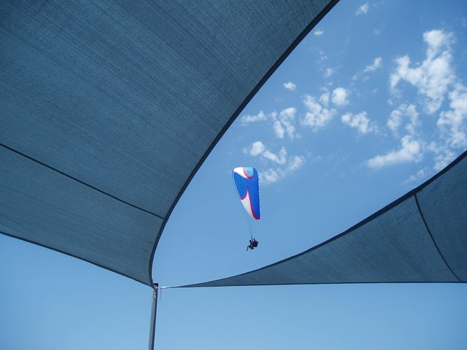 Paragliders sailing over the shade canopy at the Cliff Hanger Café located at the Torrey Pines Glider Port.