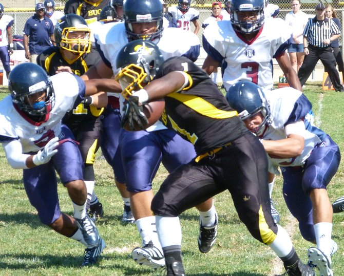 Mission Bay junior running back Devante Kinder stretches for extra yards against in front of two Horizon defenders
