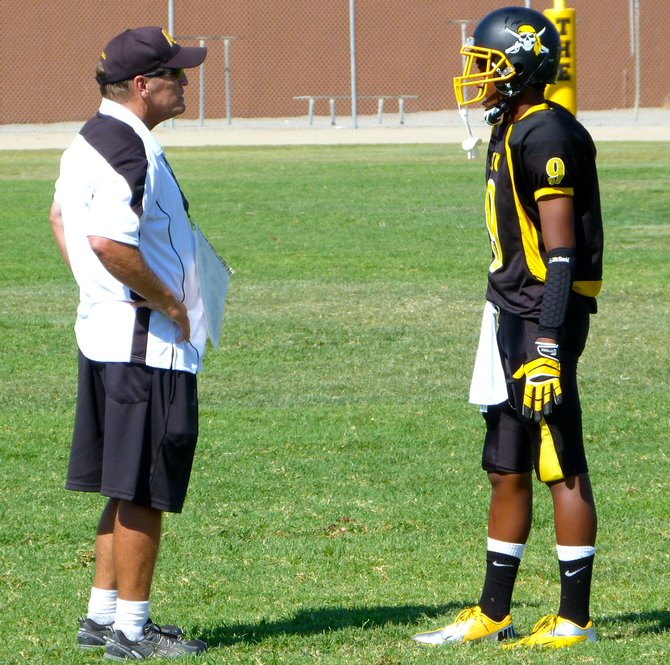 Mission Bay head coach Willie Matson talks with Buccaneers sophomore quarterback Devon Johnson