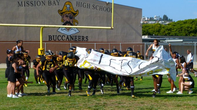 Mission Bay players burst through the banner after halftime
