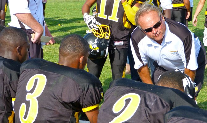 Mission Bay assistant coach Mel Galli talks to the Buccaneers defense on the sidelines