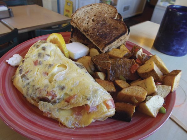 The Aswan Dam omelet features three eggs, gyro filling, red onions, tomato, and chunks of feta cheese.