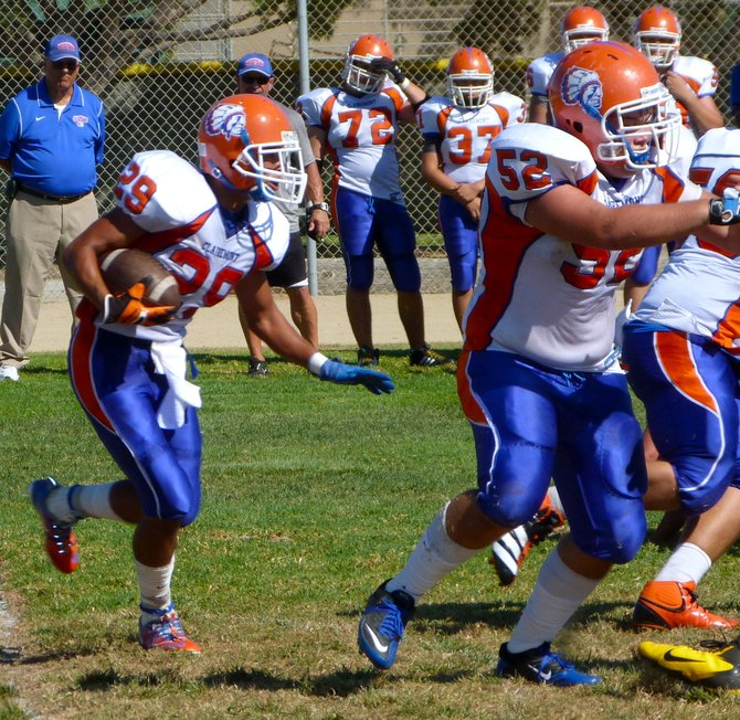 Clairemont senior running back Nick Espinoza looks for space behind a wall of blockers