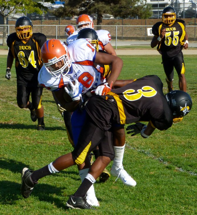 Clairemont senior receiver Chris Kelly fights through the tackle attempt of Mission Bay defensive back No. 3