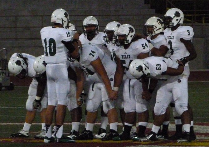 Helix junior quarterback Josh Harris gives the play to the Highlanders offense in the huddle