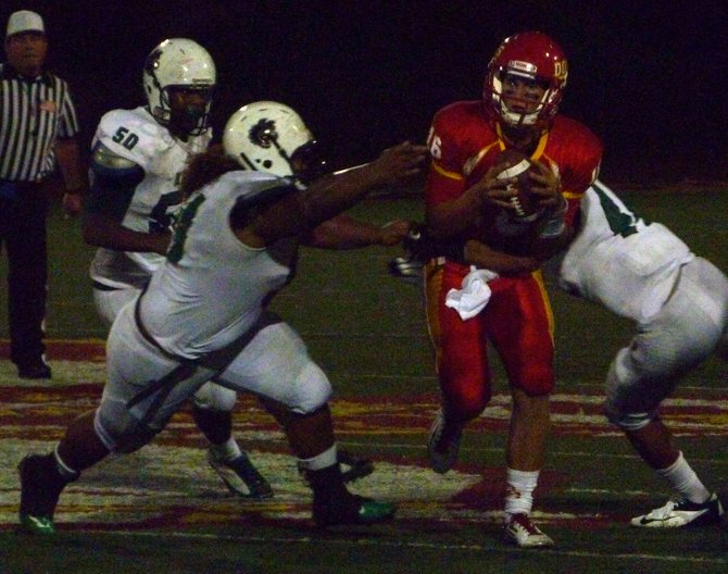 Cathedral Catholic quarterback Garrett Bogart scrambles between a trio of Helix pass rushers