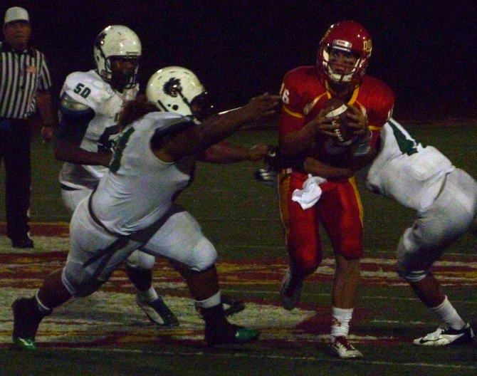 Cathedral Catholic quarterback Garrett Bogart scrambles between a trio of Helix pass rushers