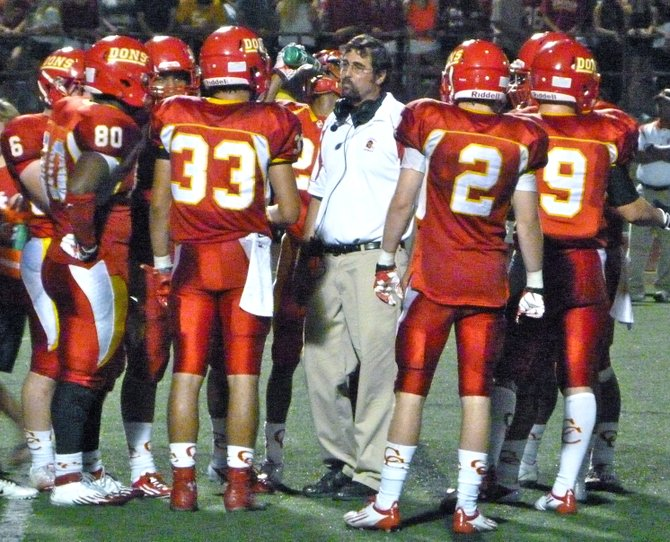 Cathedral Catholic players huddle up around Dons defensive coordinator John Montali during a timeout