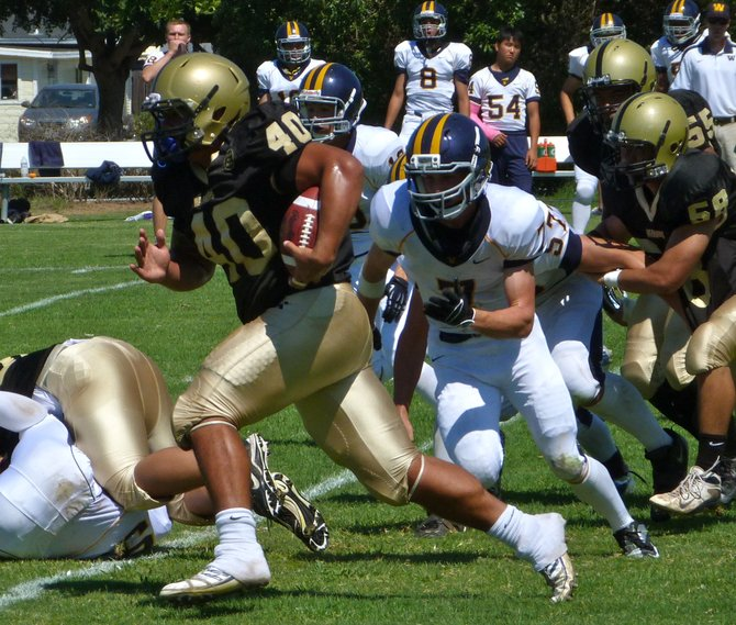 Army-Navy senior running back Joe Naotaola runs through the Webb defense
