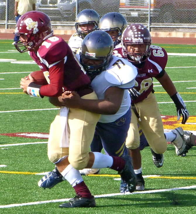 Morse junior defensive lineman Darian Savage grabs hold of Point Loma senior quarterback Branden Martin