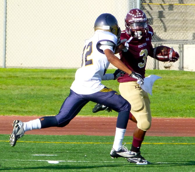 Point Loma junior running back D.J. Lacy applies a stiff arm to Morse senior safety Kevin Ritualo
