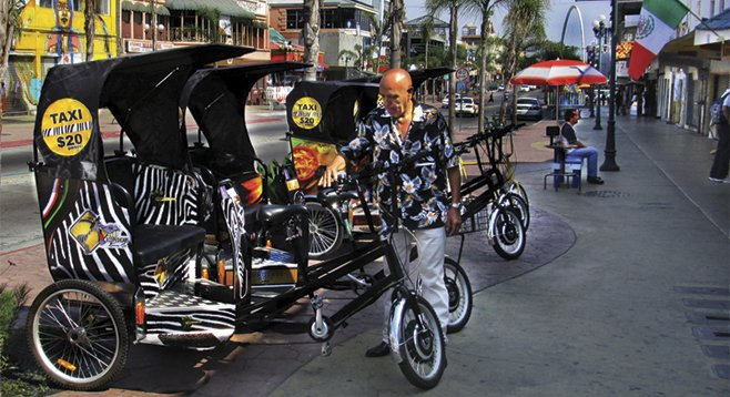 """Pedicabista"" Hector inspects his pedicab before heading to his route.  The zebra stripes and logo pay homage to Tijuana's infamous ""Zonkeys."""